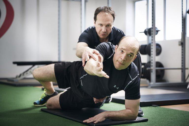 Male being given training from head personal trainer
