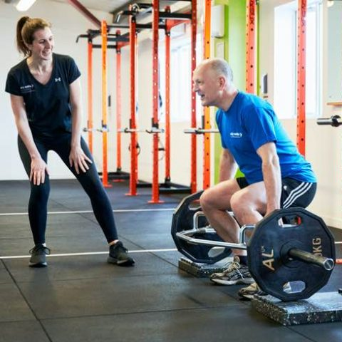 Man lifting weight being watched over by a female personal trainer