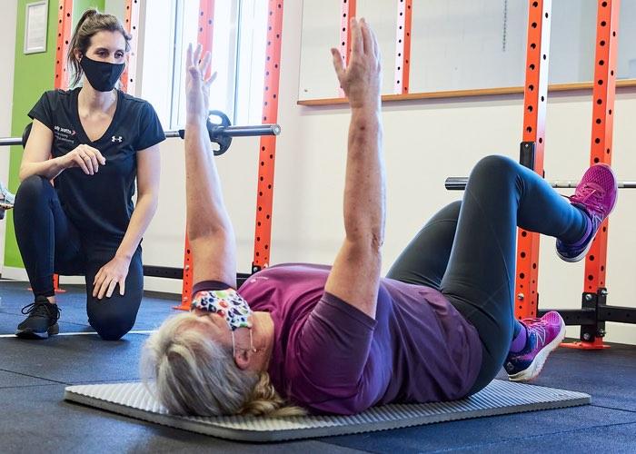 Personal Female Trainer training lady lying on floor