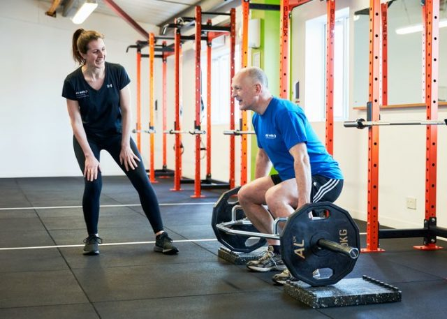 A Male lifting weights overseen by Ellie one of our female personal trainers