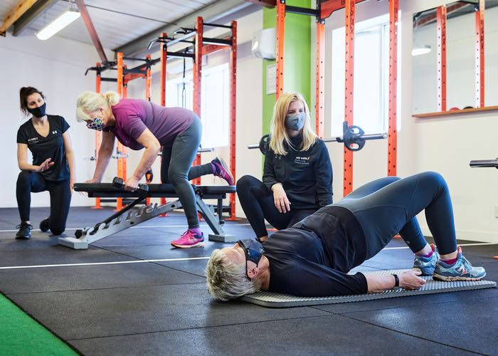 2 female personal trainers with their clients