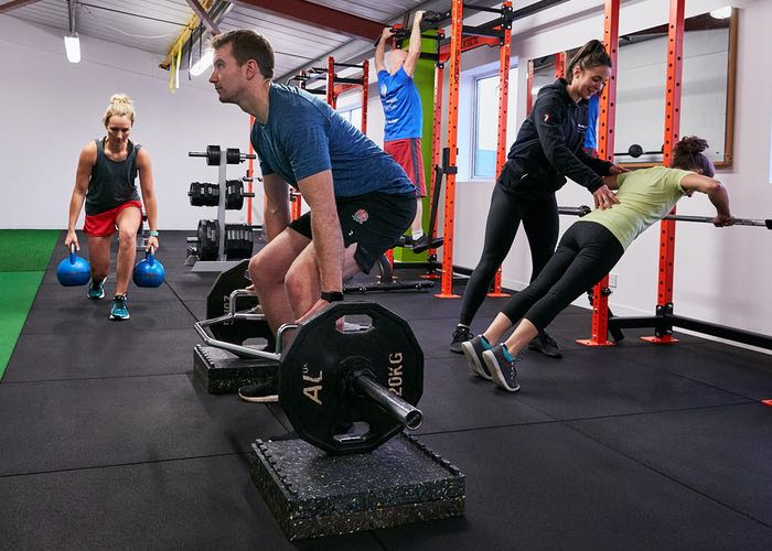 Small Group Training with a man lifting weights