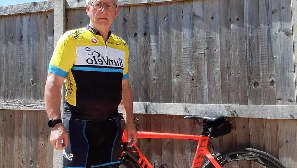 Steve Reeves standing by his bike