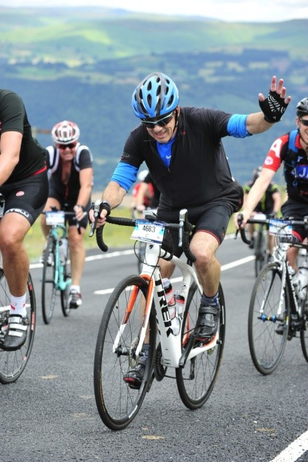 A man achieving his goal and riding a bike up hill waving