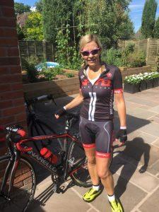 A female in biking clothing next to a bike